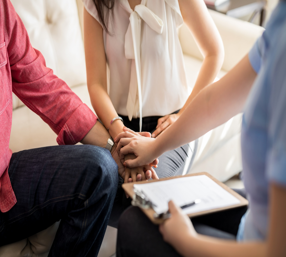 Psychologist holding hands of couple during a therapy session. Marriage counselor supporting young couple.